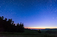 The northern circumpolar constellations including Ursa Major and Minor, the Big and Little Dippers, and Polaris, as shot from Reesor Ranch in the Cypress Hills, Alberta. Taken at 3 am with dawn twilight breaking and some low noctilucent clouds on the horizon.<br /> <br /> This is a single 30 second exposure at f/2.8 with the 16-35mm lens and Canon 6D at ISO 2000. Star glows added in Photoshop to emphasize Big Dipper and Polaris.