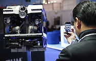 © Rob Arnold 11/03/2014. London, UK. A man taking a photo of a Remotely Operated Vehicle (ROV) at Oceanology International (OI) 2014, the world's largest exhibition for marine science and technology, which is held at London's ExCeL Centre. The three day exhibition provides an opportunity for industry, academic and government organisations to share knowledge and promote improvements in technology and strategy used for operating, surveying, protecting and exploiting resources in the oceans of the world. Photo Credit : Rob Arnold