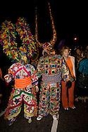 Two revelers dressed in elaborate costumes