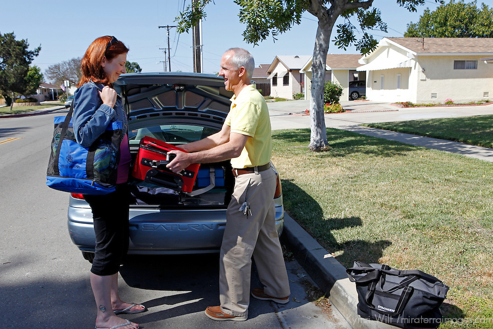 Couple packing bags in  trunk of car for roadtrip.