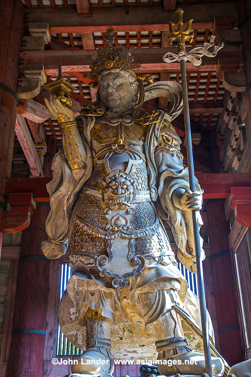 "Tamon-ten Guardian at Daibutsuden, Todaiji - Todai-ji or the Eastern Great Temple in Nara - the Great Buddha Hall Daibutsuden shelters the world's largest bronze statue of the Buddha known in Japanese as Daibutsu.  The temple also serves as the Japanese headquarters of the Kegon sect of Buddhism. The temple is a listed UNESCO World Heritage Site as ""Historic Monuments of Ancient Nara"".  Wild deer, regarded as messengers of the gods in the Shinto religion, roam the area regularly."