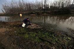 A villager from Dongtan Village walk along the polluted river covered with algae separating the village and the Jinhuarun Chemical Industry plant in Zekou Town, Qianjiang City of Hubei Province, China 15 January 2013. The villagers used to use the water and fish from the river before the arrival of the chemical plants but now the river is so polluted from discharge by the factories that they can no longer find any fish in it. While the heavy smog in Beijing and much of northern China in recent days have caused alarm among residents and renewed scrutiny on the pollution woes of the country, villagers in a small town of Hubei Province have been grappling with severe air, water and noise pollution on a daily basis over the past two years. China's Xinhua news reported 04 January 2013 that more than 60 cancer deaths in various villages of Zekou Town has been caused by the heavy pollution from the chemical industry park nearby. About 20 or more chemical plants built around the villages of Dongtan, Xiangnan, Zhoutan, Sunguai, Qingnian and others over the past two years has created huge increases in noise, air and water pollution. Many villagers complained of intensifying respiratory, heart, skin and circulatory illnesses caused by the pollution and a large spike in cancer diagnoses and deaths since the factories were built. .
