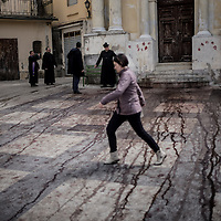 A young girl cross the main square of Nocera Terinese tryng to avoid the blood left by the Battenti after the flagellation