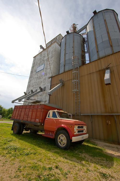A rusty grain truck rests at an old style grain elevator in Ashton, IL.
