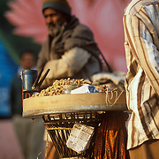 An old man walks by a  Mungfali (groundnuts) vendor on the ghat in Varanasi.