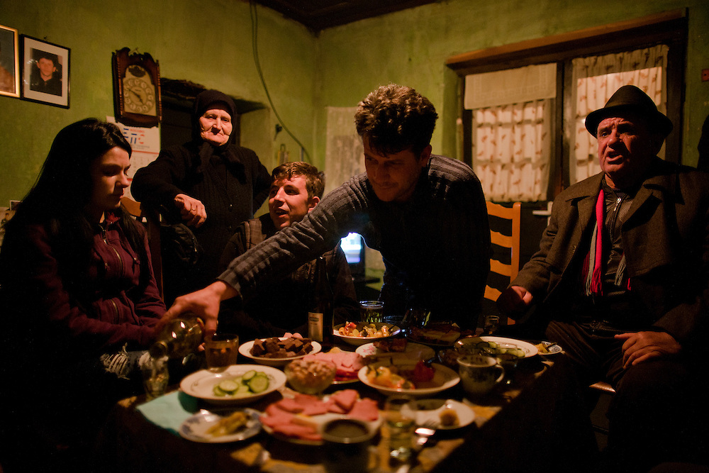 Zivana Pavlovic's home in Velika Hoca. Her younger son Nebojsa was abducted and killed during the war and is survived by his older brother Slavisa (pouring rakija)...Orthodox Christmas (January 7) in the Serbian village of Velika Hoca, Kosovo.
