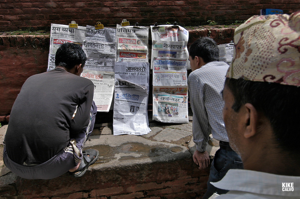 Men reading newspaper. Hanuman-dhoka Durbar Square. At the heart of the city, a complex of temples ahd shrines, both Hindu and Buddhist. B1276