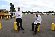 Irish Traveller men taking a cigarette break from a holy communion celebration on a site in West Drayton, near London.