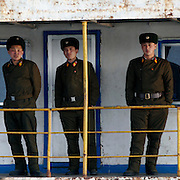 Three North Korean soldiers stand on a boat in the bank of the Yalu river in a in Sinuiju, North Korea on Wedenesday, Feb. 07, 2007. As The Six Party talks will resume on the 8th of February and the US hope to terminate North Korean nuclear program