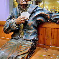 Annie Oakley on Bench with Cigar and Cards at Wall Drug Store in Wall, South Dakota<br /> &ldquo;If you can&rsquo;t beat &lsquo;em, join &lsquo;em.&rdquo; This might have been the motto of a traveling-show marksman named Frank Butler. He lost a high-stakes shooting contest to 15 year-old Phoebe Ann Mosey in 1875. He married the future Annie Oakley the following year. They went on to fame in the Buffalo Bill&rsquo;s Wild West Show. She continued setting shooting records until her death at 66. This hand-carved, cedar sculpture of Annie sitting on a bench with playing cards and smoking a cigar is in the equally iconic Wall Drug Store in Wall, South Dakota.