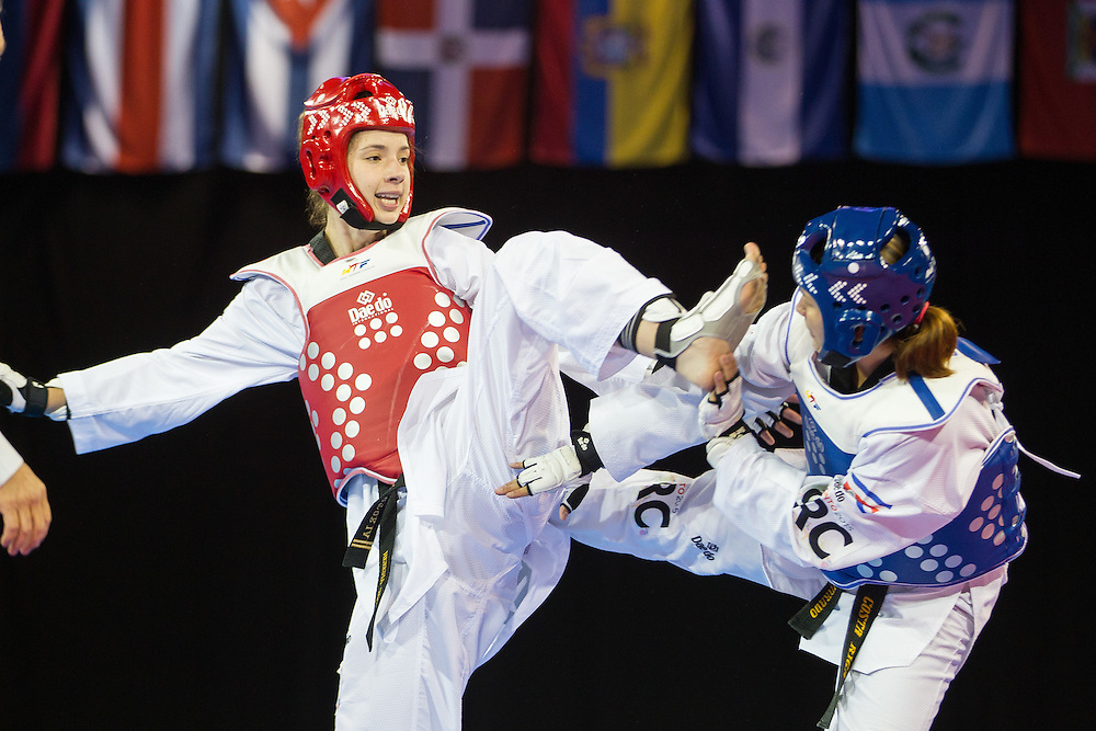 Victoria Heredia of Mexico kicks Katherine Alvarado of Costa Rica during their semi-final contest in women's taekwondo -67 kg division at the 2015 Pan American Games in Toronto, Canada, July 21,  2015.  AFP PHOTO/GEOFF ROBINS