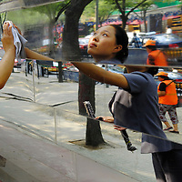 Migrant woman at work cleaning the stepped mirrored exterior of a contsruction site in the city centre...From China [sur]real © Mark Henley..