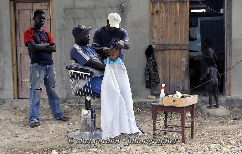 Barber cuts the hair of a young boy seated on his father's lap at an outdoor barbershop in Jimani, Dominican Republic on Tuesday, January 26, 2010.  © Chet Gordon/THE IMAGE WORKS