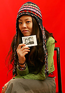 Luo Su, 30, a lay-out artist for an English-language entertainment magazine, holds her paents picture as she poses for a portrait in Beijing Dec. 3, 2005. She thinks too many young Chinese only admire foreign - read: Western - culture, and that makes her sad.(AP Photo/Elizabeth Dalziel)