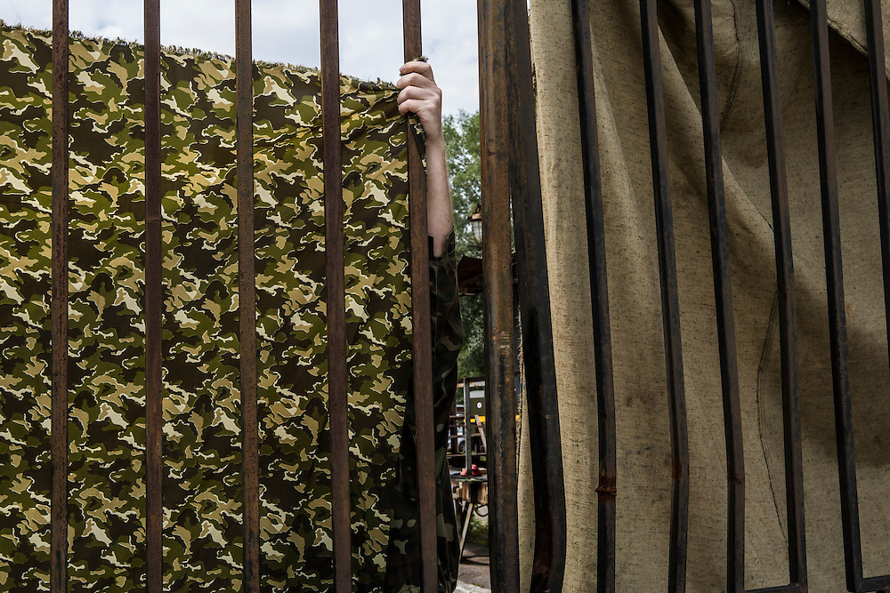 KHARKIV, UKRAINE - JULY 22: A camoflage sheet is hung to block the view through a gate of the Malyshev Factory, a state-owned producer of heavy machinery where a train transporting the victims of Malaysia Airlines flight MH17 was taken on July 22, 2014 in Kharkiv, Ukraine. The bodies of the victims are expected to be flown to Amsterdam later today. Malaysia Airlines flight MH17 was travelling from Amsterdam to Kuala Lumpur when it crashed killing all 298 on board including 80 children. The aircraft was allegedly shot down by a missile and investigations continue over the perpetrators of the attack.  (Photo by Brendan Hoffman/Getty Images) *** Local Caption ***