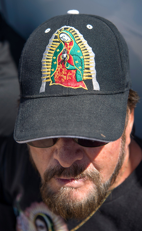 em041417j/a/Simon Garcia, from Ponderosa, wears an Our Lady of Guadalupe hat after walking to the Santuario de Chimayo, Friday April 14, 2017. With beautiful weather, huge numbers of people were making the Good Friday pilgrimage to the Northern New Mexico church.  (Eddie Moore/Albuquerque Journal