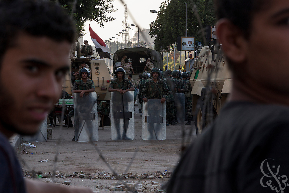 Supporters of deposed Egyptian president Mohamed Morsi watch members of the military and police force from behind barbed wire barricades at the edge of now the month long demonstrations and sit-in around the Rabaah al-Adawia mosque and square in the Nasr City district of Cairo Friday July 26, 2013.  The supporters are demanding the reinstatement of the deposed President and are opposed to the Egyptian military, which they say has undertaken an undemocratic coup.