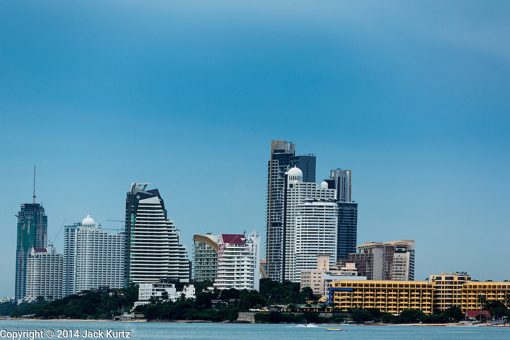 """26 SEPTEMBER 2014 - PATTAYA, CHONBURI, THAILAND:  High rise hotels on the north end of Pataya Beach. Pataya, a beach resort about two hours from Bangkok, has wrestled with a reputation of having a high crime rate and being a haven for sex tourism. After the coup in May, the military government cracked down on other Thai beach resorts, notably Phuket and Hua Hin, putting military officers in charge of law enforcement and cleaning up unlicensed businesses that encroached on beaches. Pattaya city officials have launched their own crackdown and clean up in order to prevent a military crackdown. City officials have vowed to remake Pattaya as a """"family friendly"""" destination. City police and tourist police now patrol """"Walking Street,"""" Pattaya's notorious red light district, and officials are cracking down on unlicensed businesses on the beach.    PHOTO BY JACK KURTZ"""