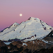 The full moon is about to set behind Mount Baker just before sunrise at Artist Point in the North Cascades of Washington state. Mount Baker, at 10,781 feet (3,286 meters), is the third largest volcano in Washington and last erupted in 1880.