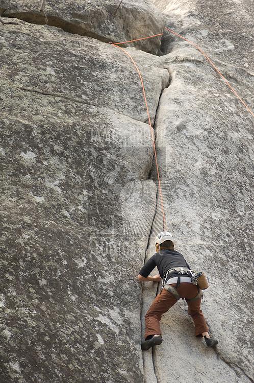 Person climbing the rock face of a mountain