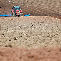 Tractor forming beds before soil separation and planting of potatoes