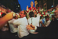 Celebrants at the Feast of San Gennaro shoulder a statue of the saint in New York City's Little Italy. This festival began in Naples, where it remains a one-day religious event.