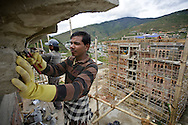 Indian migrant laborers work at the construction site outskirts of Thimphu, Bhutan on September 2, 2013. The population in the city is rapidly growing as people, especially young generations, from the rural area are moving into the city to search for jobs, causing massive housing demands.<br /> (Photo by Kuni Takahashi)