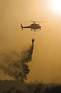 Helicopter dumps water on Desert Hills fire.