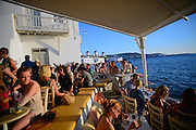 Visitors enjoy sunset in Mykonos from terrace with windmills in view, Greek Islands, Greece