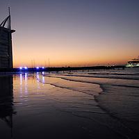 Seven star Burj Al Arab luxury hotel in Jumeirah Beach at sunset, famous for its gaudy post-modern Arabian interior. Arabian Gulf. Dubai<br />