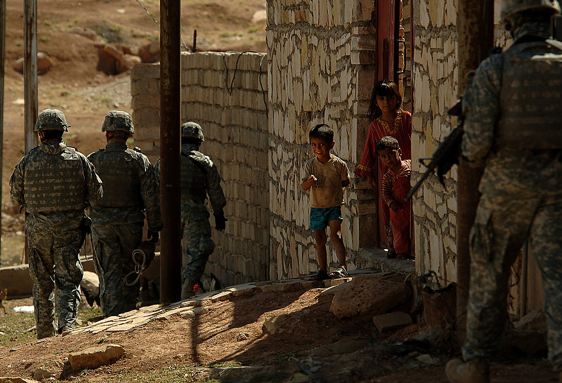 A young Iraqi boy comes out to meet the soldiers from Bravo Company 1/17th Infantry 172nd Stryker BDE Ft. Wainwright, Alaska, who are patrolling the streets of Al Tanak, Mosul, Iraq May 25, 2006. — © TSgt Jeremy Lock/