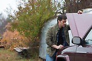 man looking under the hood of a suv near his airstream in the woods