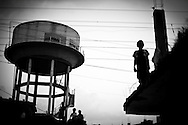 Bhopal, twenty-five years later..Children play on roofs near a water tower in the city of Bhopal in the state Madhya Pradesh, Indai October 8, 2009. ..Twenty-five years after a gas leak in the Union Carbide factory in Bhopal killed at least eight thousand people, toxic material from the 'biggest industrial disaster in history' continues to affect Bhopalis. A new generation is growing up sick, disabled and struggling for justice...The effects of the disaster on the health of generations to come, both through genetics transferred from gas victims to their children and through the ongoing severe contamination, caused by the Union Carbide factory, has only started to develop visible forms recently...