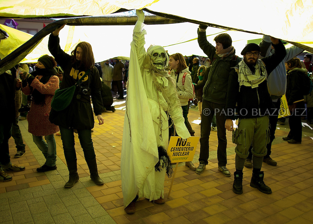 A man dressed as the 'Death' and people attend a demonstration organized by environmentalists against the possible construction of a nuclear waste storage in Villar de Cañas, near Cuenca , on February 12, 2012. Placards read 'Agains the nuclear cemetery.