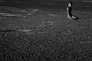 Child playing in mud in Metihaut. @ Martine Perret. 17 May 2002