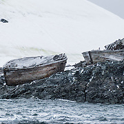 Old wooden boats survive from the whaling era, near a white glacier on an island offshore from the Antarctic Peninsula.
