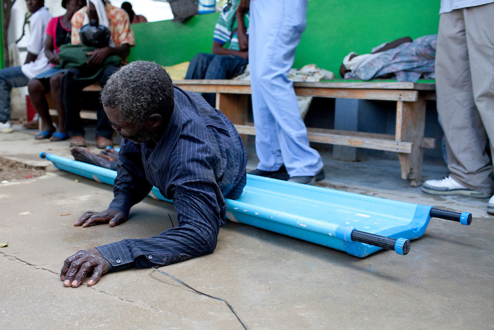 A cholera patient rolls over to vomit after being brought to the hospital on a stretcher on Sunday, October 31, 2010 in Petite Riviere, Haiti.
