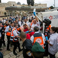 With the Western Wall, the holiest site where Jews can pray in the background, Israeli medics evacuate a wounded man following a stabbing attack in Jerusalem's Old City, Wednesday, Oct. 7, 2015. A Palestinian woman stabbed the Israeli man who then shot and wounded her in the Old City <br /> Photo by Olivier Fitoussi.