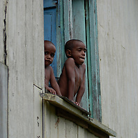 Two young Fijian boys peer from a window.  Mountain village, Vanua Levu island, Fiji.