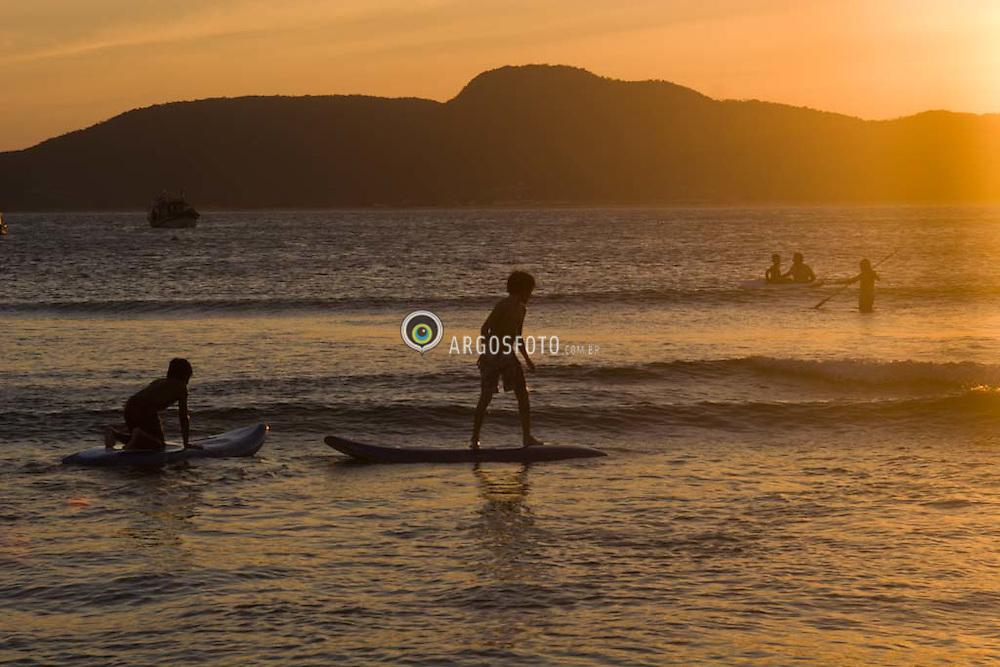 Menino se equilibra na prancha de surf./Boy balances on a surfboard.