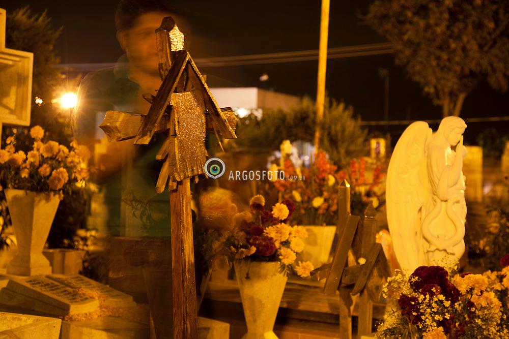 Homenagem aos mortos no cemiterio em  San Andres Mixquic no Mexico. Dia dos Mortos e uma celebracao de origem indigena, que honra os defuntos no dia 2 de novembro. Inicia no dia 1 de novembro e coincide com as tradicoes catolicas do Dia dos Fieis Defuntos e o Dia de Todos os Santos./   Homage to the dead in the cemetery in San Andres Mixquic, Mexico. Day of the Dead (Spanish: Día de los Muertos) is a Mexican holiday. The holiday focuses on gatherings of family and friends to pray for and remember friends and family members who have died. It is particularly celebrated in Mexico, where it attains the quality of a National Holiday. The celebration takes place on November 1st and 2nd, in connection with the Catholic holidays of All Saints' Day (November 1) and All Souls' Day (November 2).