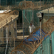 "A detainee seen through a maze of fence and wire in Camp 4 at the detention facility in Guantanamo Bay, Cuba. Camp 4 is a communal style camp where more compliant detainees live in small groups and have access to a more open air environment. Approximately 250 ""unlawful enemy combatants"" captured since the September 11, attacks on the United States continue to be held at the detention facility.(Image reviewed by military official prior to transmission)"