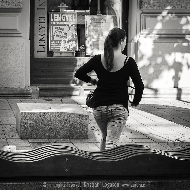 Woman walking a way from a curvy stone bench in central Budapest Hungary