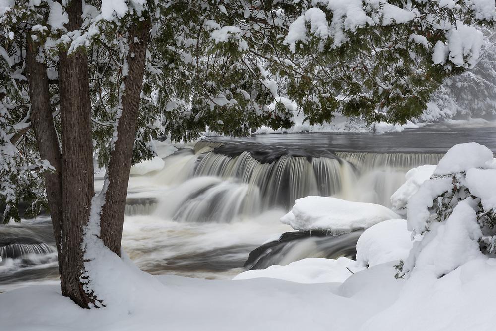 A blanket of fresh snow surrounds Upper Bond Falls in Michigan's Upper Peninsula.