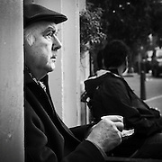 Man sitting outside a cafe in central Amsterdam drinking coffee looking at life