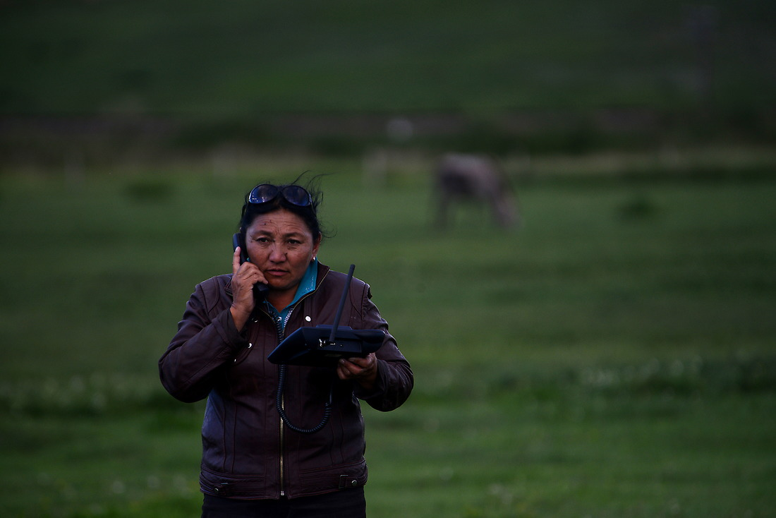 Herder Otgonjaral is making a phone call from a field behind her Ger. — © Jeremy Lock/USAF