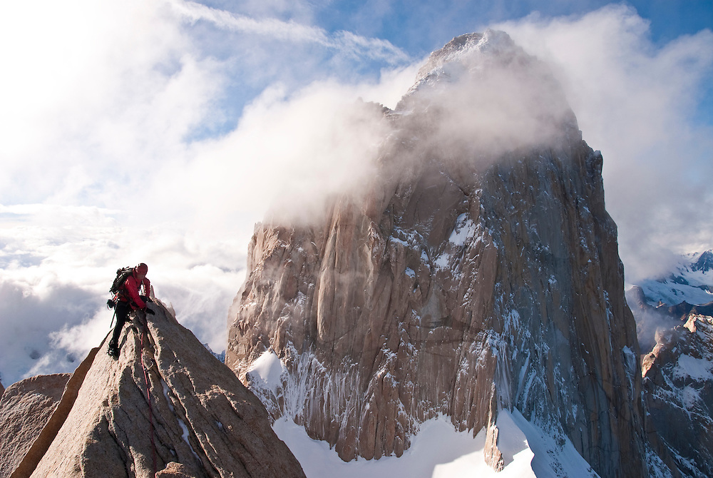 Kate Rutherford pulling onto the knife edge ridge of Poincenot.    The South Face of Fitzroy looming in the Background.  The famed Cailornia route vaguely follows the semi obscured left skyline.