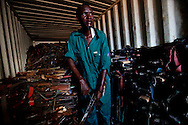 A member of the SPLA inspects guns seized during civilian disarmnament campaigns.