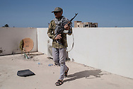 Libya: A Libya's Government of National Accord's (GNA) fighter walks on the rooftop of a building on the frontline with ISIS in Sirte. Alessio Romenzi