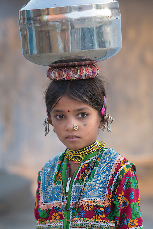 school is not an option; she is carrying water container